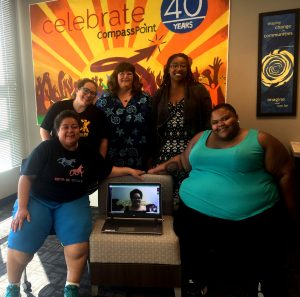 "Photo of the August 2016 Nolose board standing and sitting in front of the ""Celebrate 40 Years CompassPoint"" poster at their retreat: back row Sarah Doherty, Sally Smith, Shana McDavis-Conway; Front row Lissette Cheng, a chair with Sarah's laptop showing Cicely Smith google chatting in from Pennsylvania, and Crystal Newman. There's a window on the left side of the picture and a framed poster to the right of the large orange CompassPoint poster that says ""shaping change in communities, imagine what can be."""