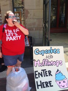 "Photo of Sarah Doherty, white midsize fat cis dyke with brown hair in ponytail, teal glasses, bluejean shorts, red shirt reading ""I'm fat let's party,"" donut backpack strap visible, with a trashbag of pants at her feet, biting into a cupcake next to the door of Cupcakes and Muffintops next to the sign that reads ""Cupcakes and Muffintops Enter Here"" with a drawing of a cupcake. It's sunny and Sarah looks happy."