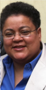 Lissette's headshot: Image of Lissette's head and shoulders: a brown skinned black short curly haired queer midsize woman, in small rectangular glasses, a white suit jacket, and collared blue shirt, smiling.