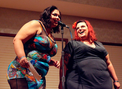 Photo of two glamour femmes speaking at the mic.
