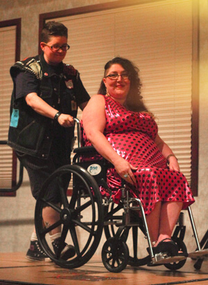 Photo of dapper butch wheeling glamorous femme (wearing a sparkly dress) in her wheelchair