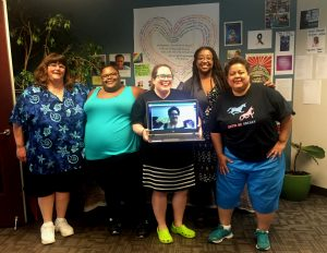 The Nolose board at the end of the retreat, standing in front of CompassPoint's racial justice display, which has plants and posters and images of racial justice activists. Left to right are Sally, a superfat white femme, Crystal, a superfat Black femme, Sarah, a midsize white dyke, holding a laptop showing the head of Cicely, a multiracial Black nonbinary person, Shana, a midsize Black femme, and Lissette, a midsize Latinx dyke. Photo by Amy Benson.