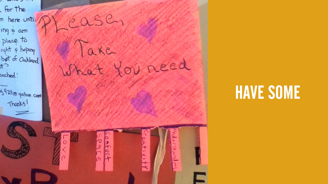 "Photo of bulletin board note: ""Please, take what you need."" Pull-off tags include ""love, space, comfort, creativity, understanding."""